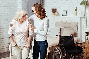 a hospice care giver helping a senior woman walk to and form her wheelchair