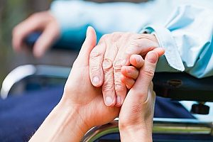 a man holding the hands of his hospice care giver as he copes with cancer