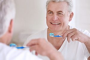 a senior man in hospice care brushing his teeth