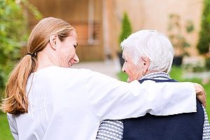 a senior woman receiving hospice care for dementia patients from her care giver