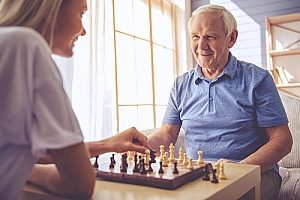 an elderly man playing chess with his hospice care provider