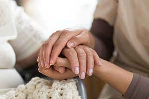 senior citizen holding the hands of her care giver as she receives hospice care for dementia patients