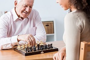a senior man playing chess with his hospice care giver