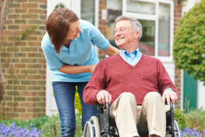 a senior man with ALS in a wheelchair smiling at his hospice caregiver