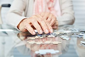 a woman in dementia hospice care attempting to complete a puzzle