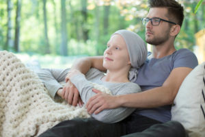 a woman suffering from cancer being supported by her husband while having in-home hospice care