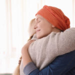 a woman with cancer in hospice care at home hugging a relative