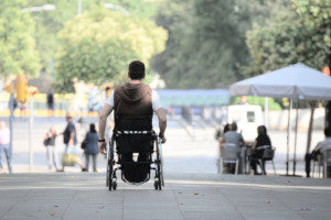 a young man afflicted with ALS in a wheelchair going towards other people