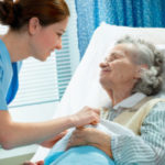 a young nurse caring for an elderly woman nearing the end of her life