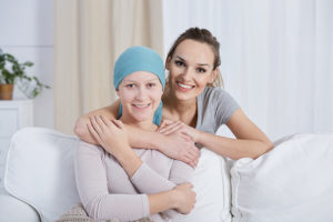 an in-home hospice caretaker hugging a cancer patient