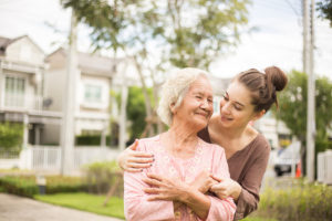 a happy elderly woman outside her home with a hospice caregiver