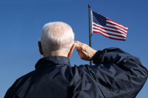 a senior veteran that is in hospice care saluting the american flag