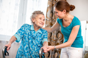 a young hospice caretaker helping a senior woman and managing her pain