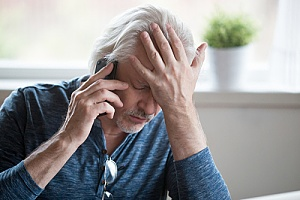 a senior man with dementia having difficulty concentrating on the phone