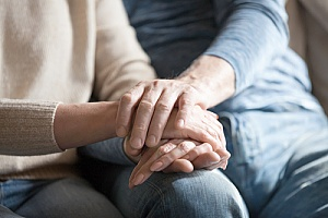 an elderly man holding the hands of his wife who is experiencing late stage dementia symptoms