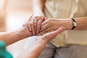 a hospice care giver holding the hands of a senior during end of life