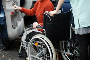 caregiver helping woman in hospice care with transportation to doctors