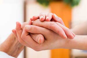 hospice caregiver holding womans hand showing what to expect from hospice care