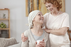 woman experiencing late stage cancer symptoms with her caregiver