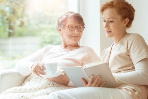 Hospice care nurse reading book to patient with illness