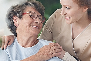 Senior woman with hospice nurse sitting and smiling on sunny day
