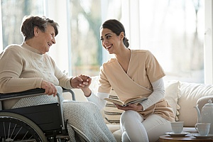 a caregiver helping a senior patient who is in end-of-life care