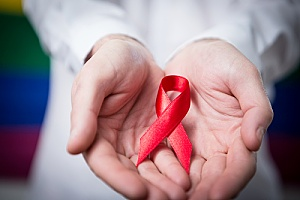 a doctor holding an HIV/AIDS ribbon representing late stage HIV/AIDS symptoms