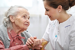 a woman in hospice receiving help and support from her caregiver