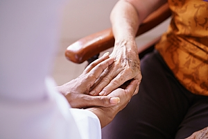 Doctor holding hand with senior patient sitting