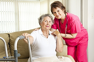 Elderly woman with walker sitting on couch smiling at camera with caregiver nurse