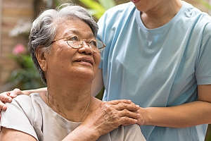 Senior woman smiling at nurse in hospice care