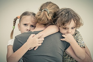 Sad children hugging mother
