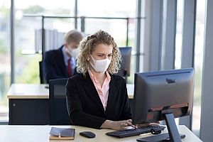 a business woman wearing a mask as she returns to work
