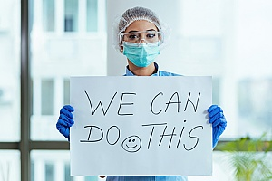 a supportive healthcare professional holding a 'We Can Do This' sign during COVID-19