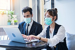 two employees discussing work with masks on