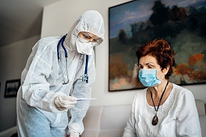 a hospice care worker tending to a patient with full PPE on