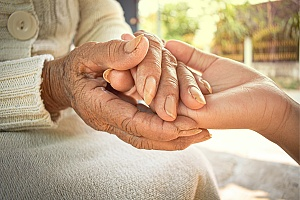 caregiver and hospice patient holding hands
