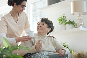 women handing a cup to her hospice patient