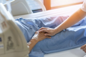 patient laying in bed with caregiver holding their hand