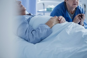 women holding hand of patient inStages Of Dying