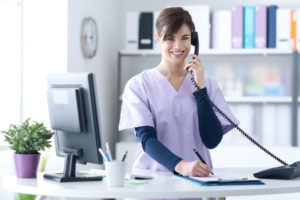 hospice volunteer answers phone call while writing something down