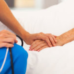 caregiver holding hands with someone in stages of dying