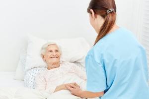 women in a bed asking about pain management in hospice