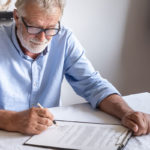 older man signing a will after learning importance of a living will