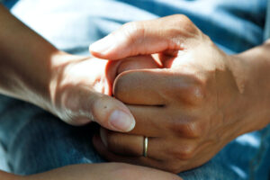 hospice patient clutches the family member hand