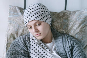 hospice patient with scarf around head lays in bed