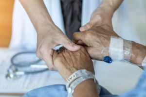 Doctor Holding Patient Hand explaining hospice care vs palliative care