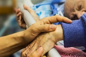 Hospice Service Person Holding Old Patient Hand after knowing hospice care vs palliative care